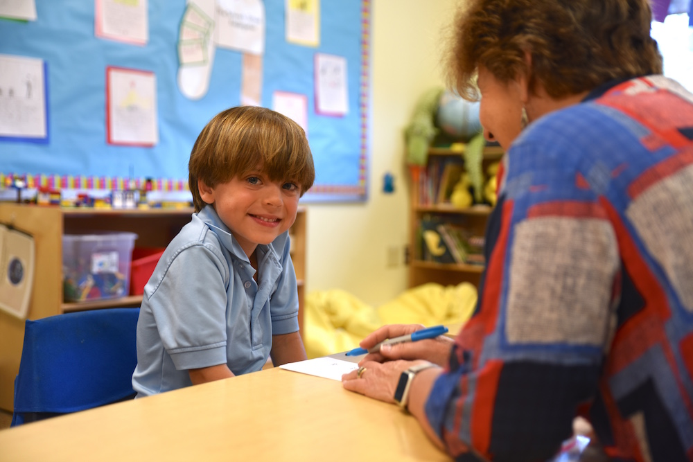smiling boy working with teacher