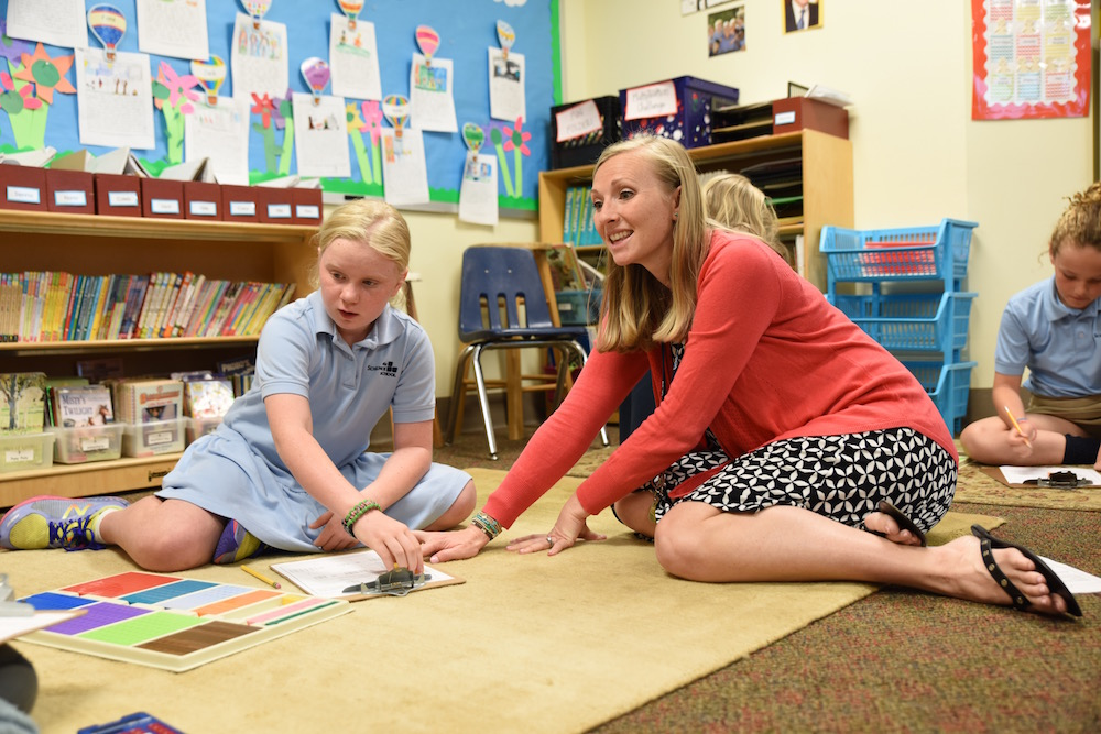 teacher on floor working with girl