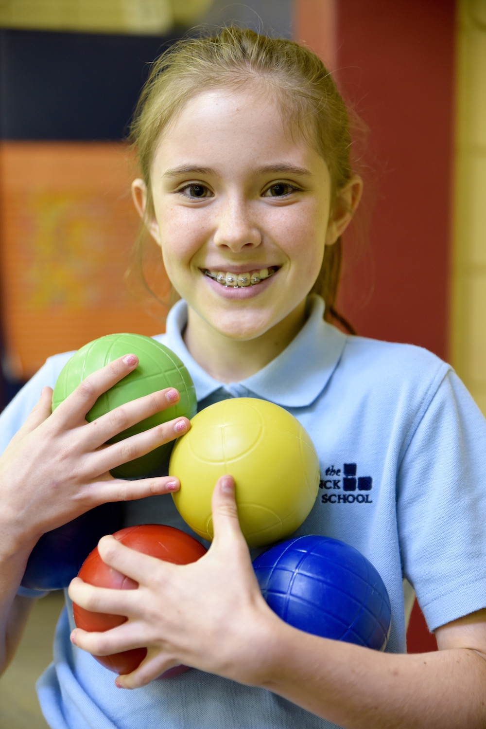 girl holding multi-colored balls