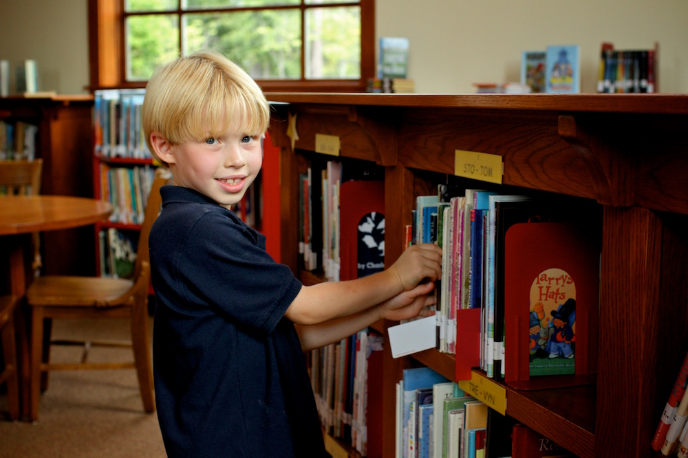 boy at book shelf in library